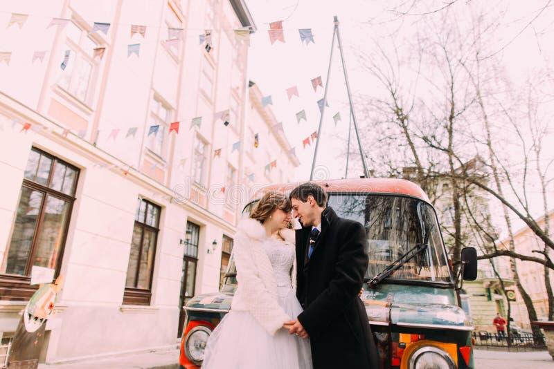 Les fronts émouvants empracing heureux de ménages mariés s'approchent de la rétro voiture colorée image stock