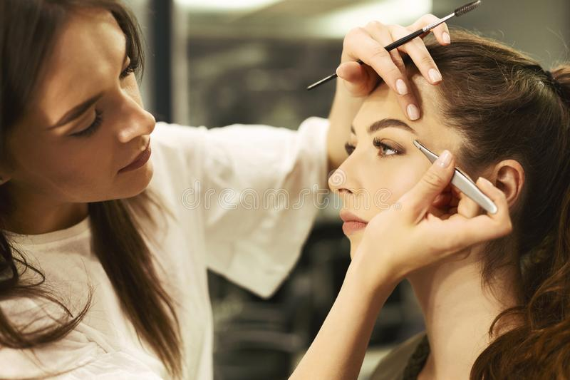Les fronts de la fille de Plucking And Shaping d'artiste de front dans le studio de beauté image libre de droits