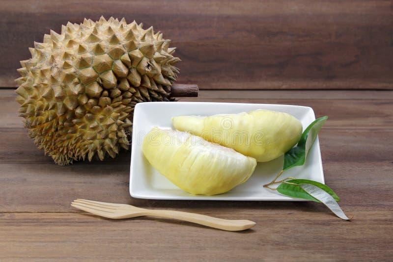 Les fruits de durian et le durian jaune de chair sur le plat blanc avec le durian poussent des feuilles, fond en bois photographie stock