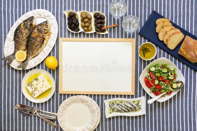 Les fruits de mer fraîchement cuits ont grillé des poissons de dorade, des sardines en huile d'olive et la salade de légume, oliv images stock
