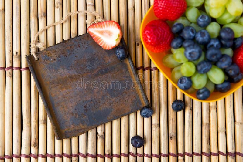 Les fruits saisonniers frais et un métal se connectent un tapis en bambou image libre de droits