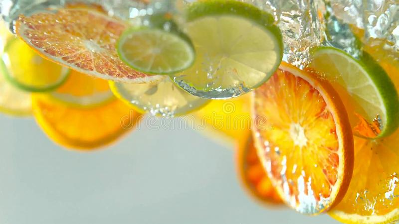 Les fruits tropicaux de citurs découpent la chute en tranches dans l'eau image libre de droits