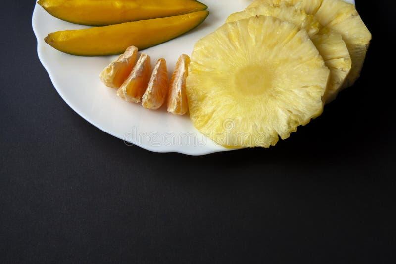 Les fruits tropicaux, la mangue, l'ananas et la mandarine découpe le pla en tranches images libres de droits