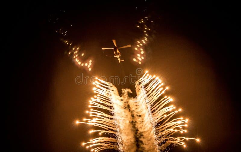Les fusées ont déchargé en un hélicoptère dans le ciel nocturne images libres de droits