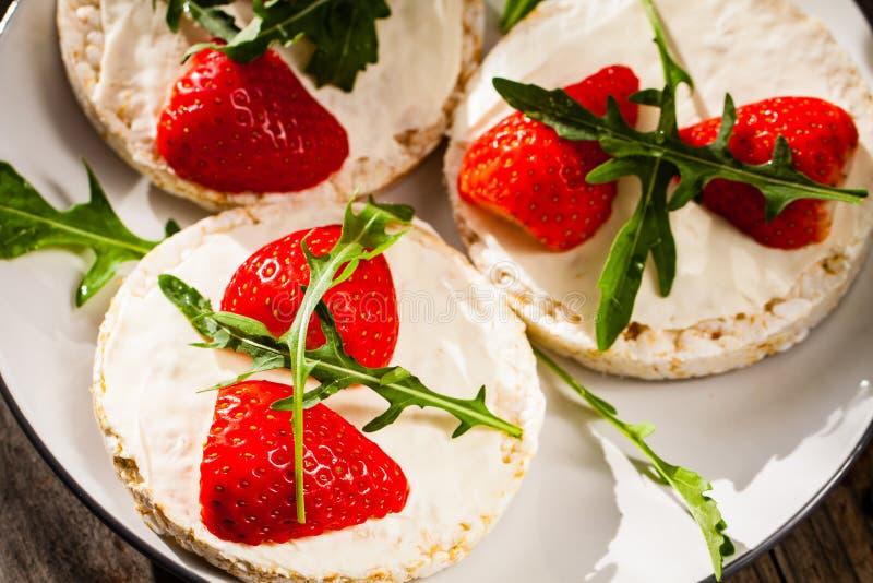Les gâteaux de riz de Multigrain avec des fraises portent des fruits, fromage de mascarpone et arugula mous photographie stock