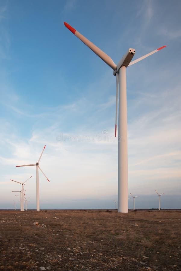 Les générateurs d'énergie éolienne à un moulin à vent cultivent dans un domaine labouré et un fond de ciel bleu photographie stock