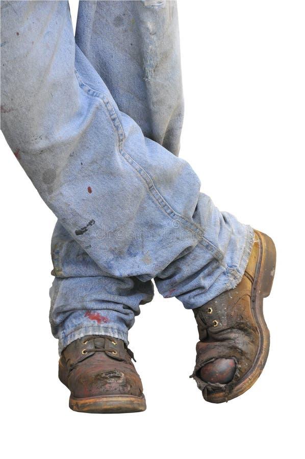Les gaines et les jeans de l'ouvrier image stock