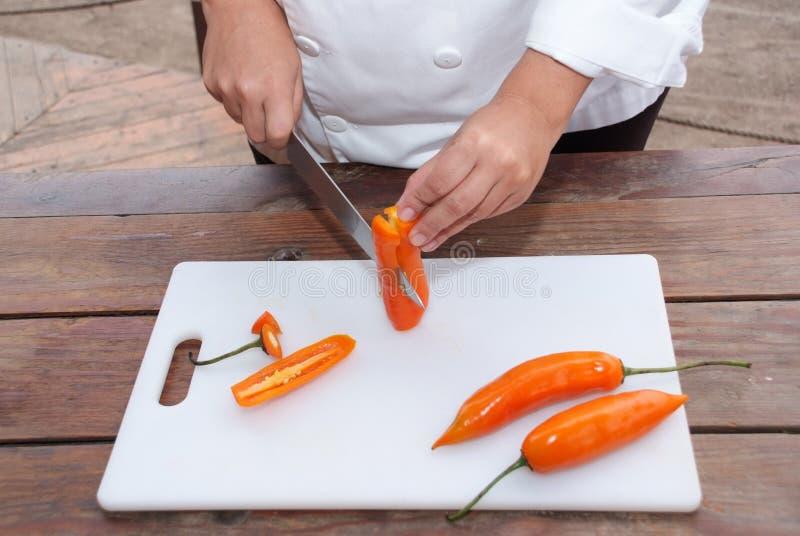 Les gants de port de chef avec un couteau pointu et nettoient l'aji de coupes image libre de droits