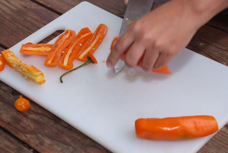 Les gants de port de chef avec un couteau pointu et nettoient l'aji de coupes photo stock