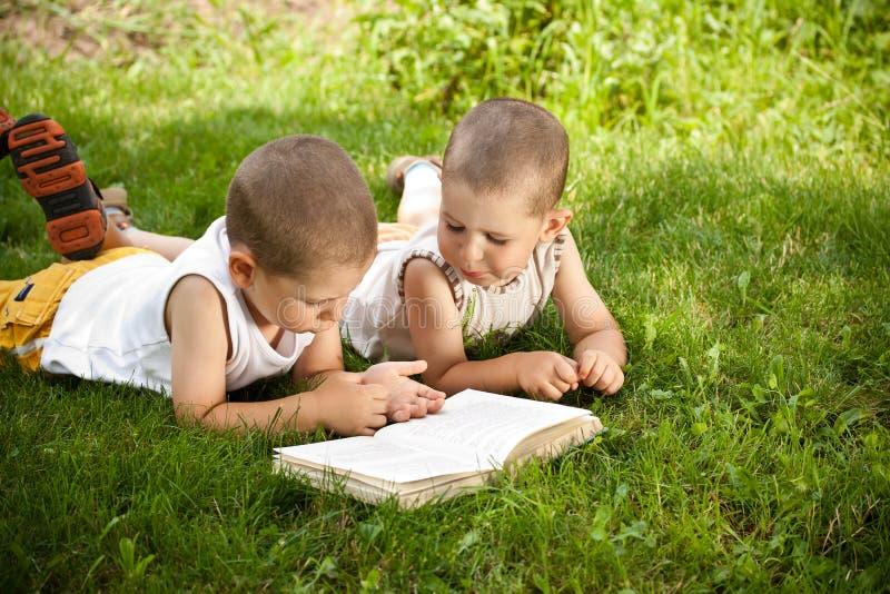 Les garçons affiche un livre photo stock