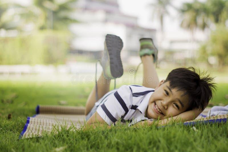 Les garçons asiatiques sont dans l'humeur à détendre le week-end en parc au soleil de matin, concept d'enfance lumineux, apprenan image stock
