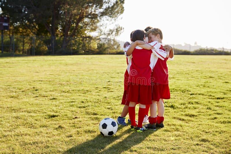 Les garçons dans une équipe de football parlant dans l'équipe se blottissent avant jeu photographie stock libre de droits