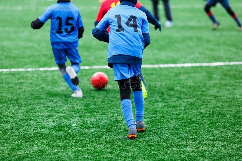 Les garçons dans les vêtements de sport rouges et bleus joue au football sur le champ d'herbe verte Partie de football de la jeun photographie stock libre de droits