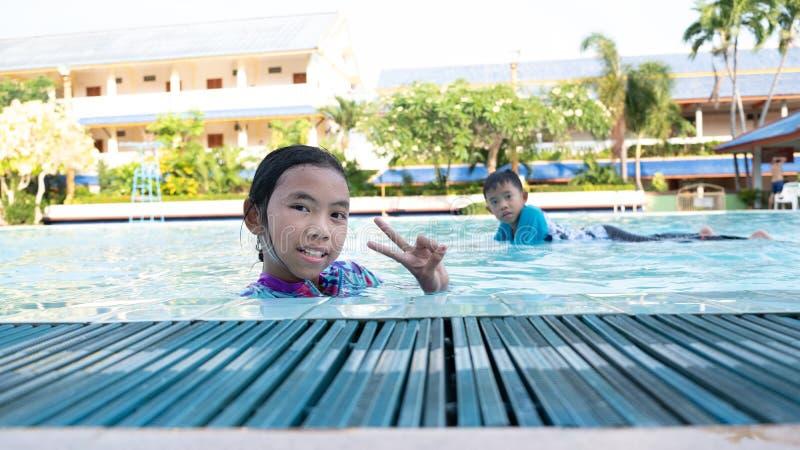 Les garçons et les filles ont l'amusement jouant dans la piscine photo stock