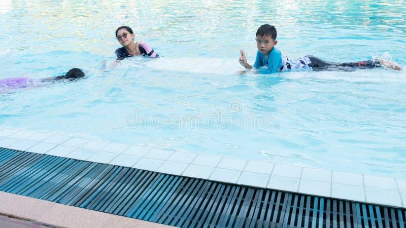 Les garçons et les filles ont l'amusement jouant dans la piscine, pendant l'été et en vacances photographie stock libre de droits