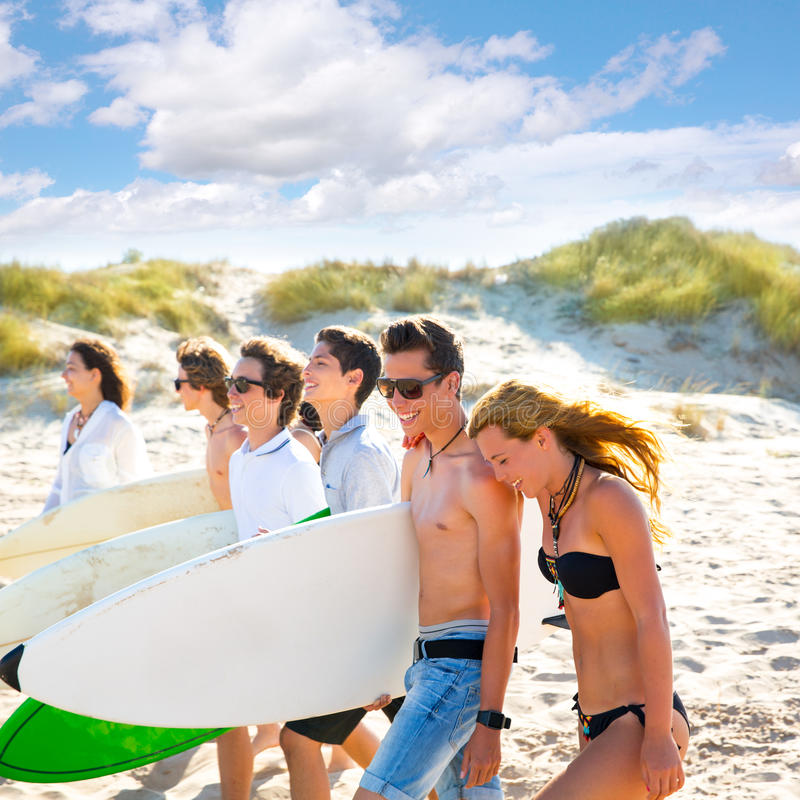Les garçons et les filles de l'adolescence de surfer groupent la marche sur la plage photographie stock libre de droits