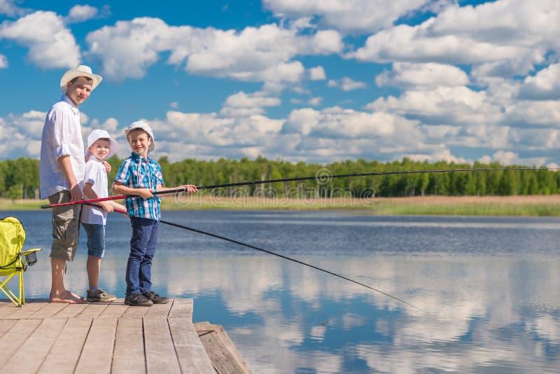 Les garçons et leur père passent un jour sur un voyage de pêche sur un soleil photo libre de droits