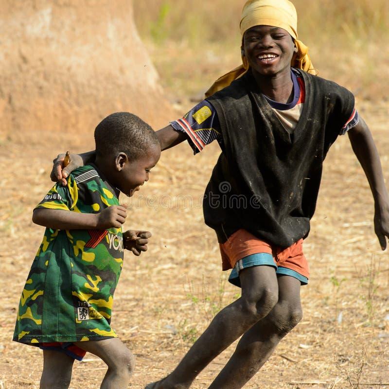 Les garçons ghanéens non identifiés jouent sur la rue dans le vill de Ghani photographie stock