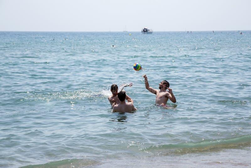 Les garçons jouant avec une boule dans l'eau sur le Barcelonetta échouent photographie stock libre de droits