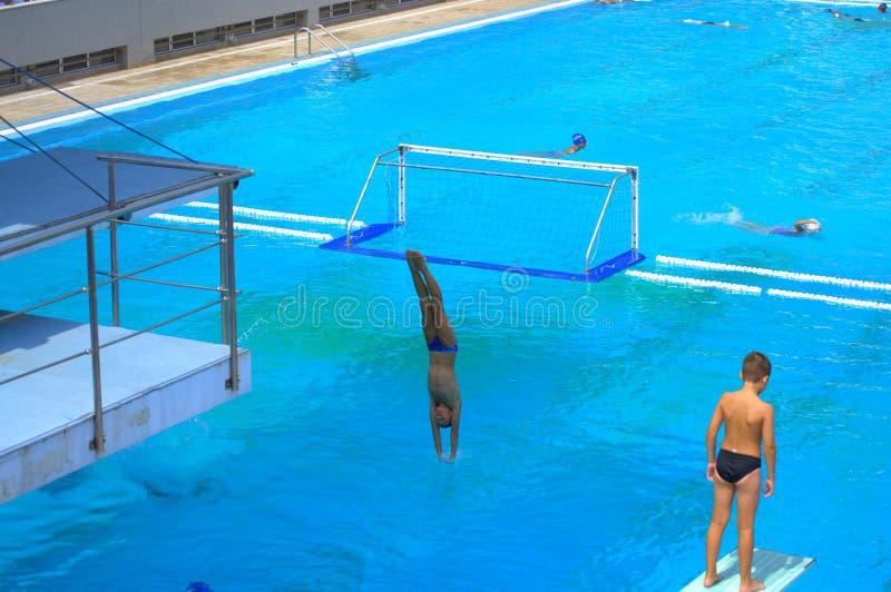 Les garçons sautant dans la piscine extérieure photos stock