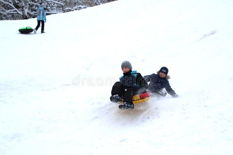 Les garçons se brisent dans l'un l'autre roulant vers le bas une colline images stock