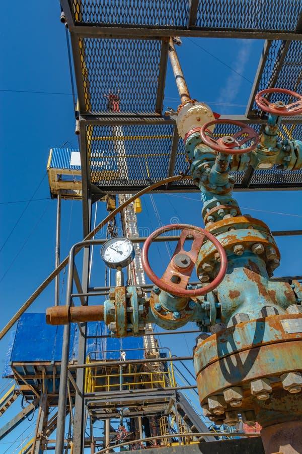 Les garnitures de fontaine pétrole le puits sur le fond de la plate-forme de forage images stock