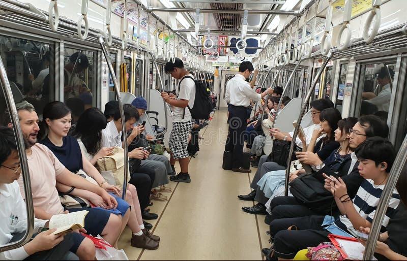 Les gens à l'aide des téléphones intelligents à l'intérieur du chariot de souterrain tout en montant Concept de manque de communi photos stock