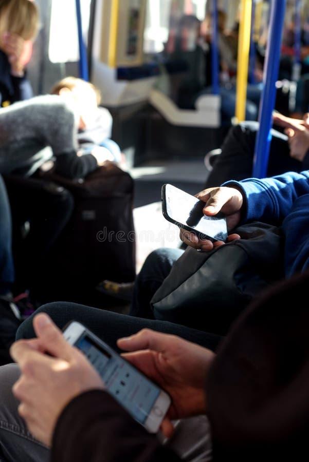 Les gens à l'aide du téléphone portable sur le train au fond de Londres photographie stock