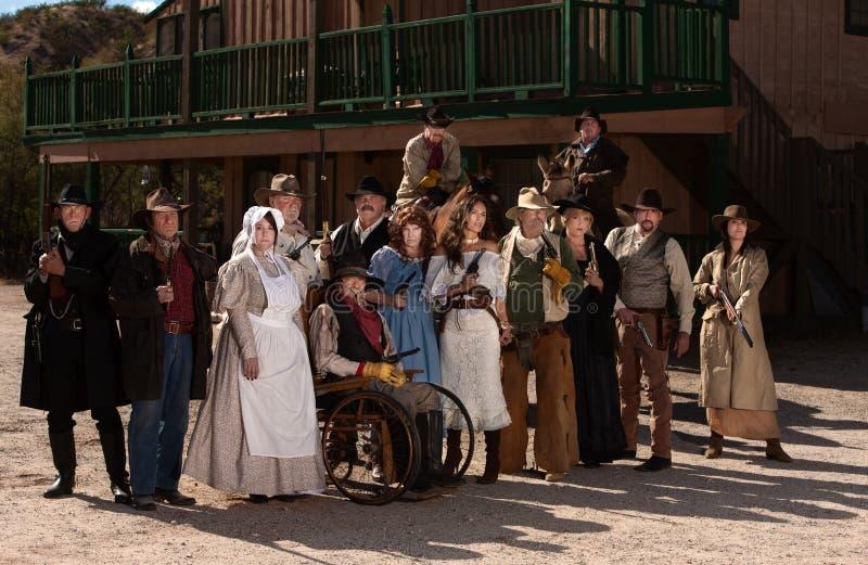 Les gens à l'extérieur d'un bâtiment dans de vieux costumes occidentaux photographie stock