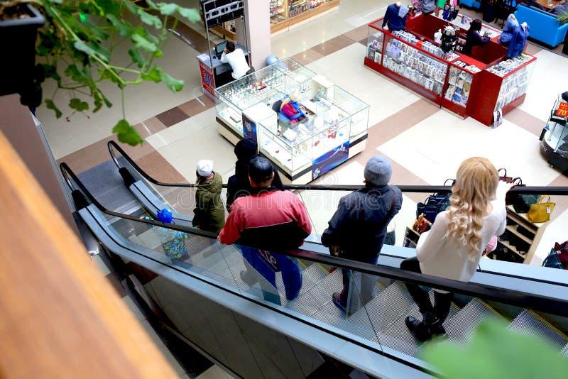 Les gens à l'intérieur de monter un escalator photo libre de droits