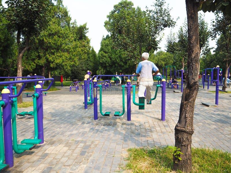 Les gens établissant sur l'équipement public en parc image stock