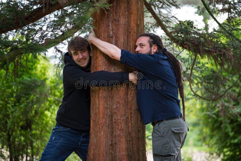 Les gens étreignant des arbres images libres de droits