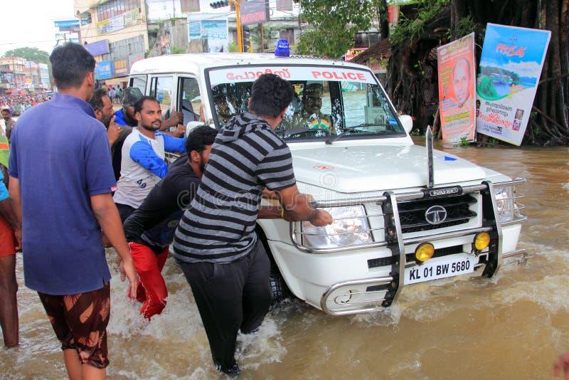 Les gens aident un véhicule pour croiser les eaux d'inondation images libres de droits