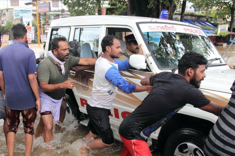 Les gens aident un véhicule pour croiser les eaux d'inondation photographie stock libre de droits