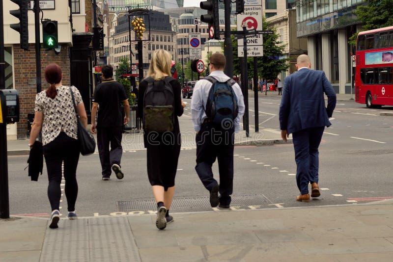 Les gens allant travailler ils passent par le croisement ils sont juste vert images libres de droits