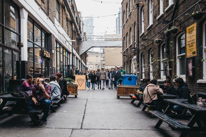 Les gens appréciant la nourriture de rue dans la cour d'Ely, ruelle de brique, Londres est, R-U image libre de droits