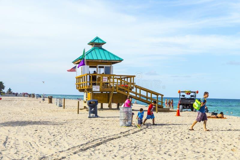 Les gens apprécient la plage aux îles ensoleillées protégées par des maître nageurs dedans photographie stock libre de droits