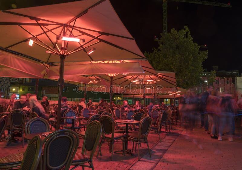 Les gens apprécient la vie nocturne sur le café extérieur dans la ville néerlandaise Groningue sous des parasols et des lampes de image stock