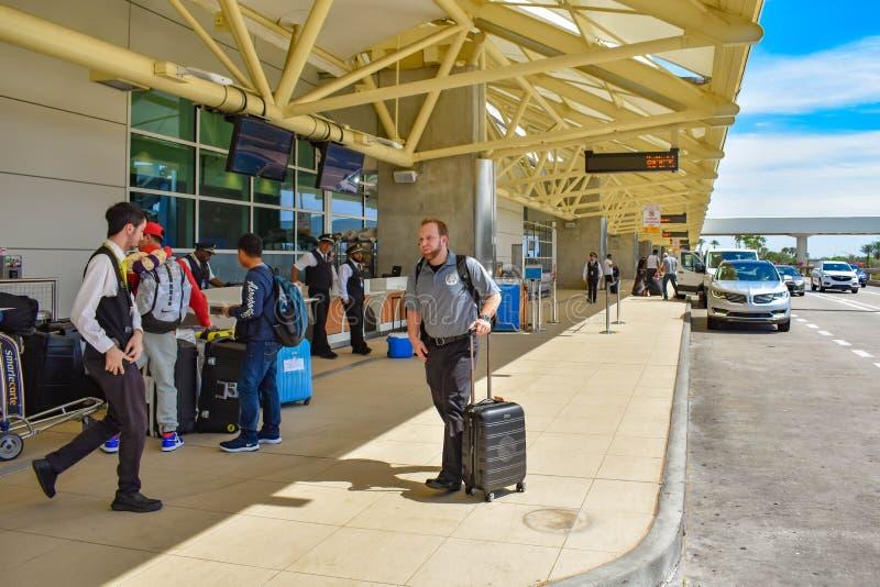 Les gens arrivant à un aéroport et vérifiant le bagage chez Orlando International Airport photographie stock libre de droits