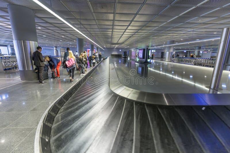 Les gens attendent leurs sacs à la ceinture de bagages dans l'aéroport de Francfort image stock