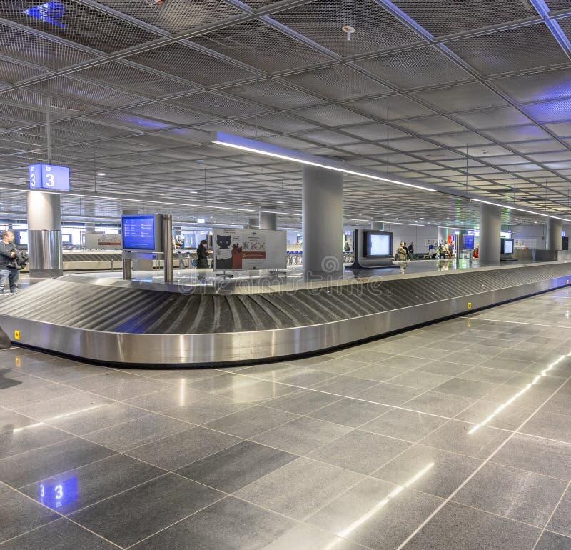 Les gens attendent leurs sacs à la ceinture de bagages dans l'aéroport de Francfort photo stock