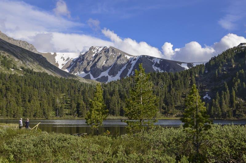 Les gens au lac dans les montagnes image stock