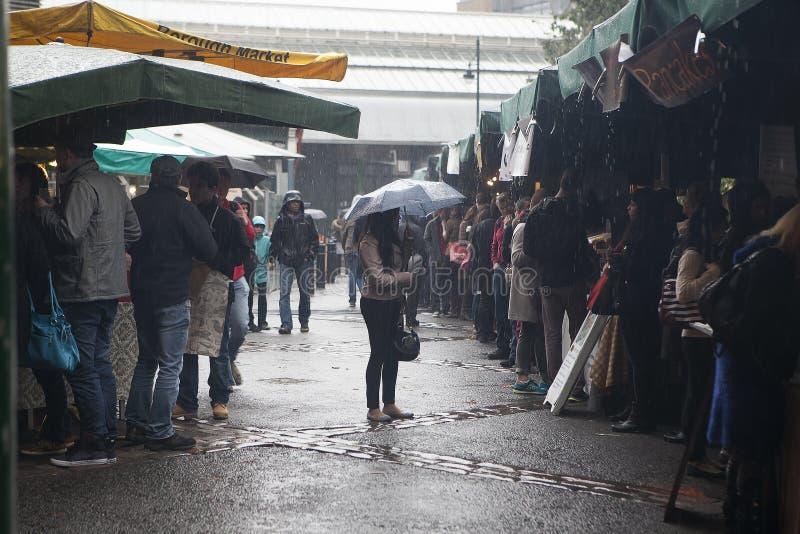 Les gens au marché de ville, se cachant de la pluie Entre les rangées il y a une fille avec un parapluie photos libres de droits