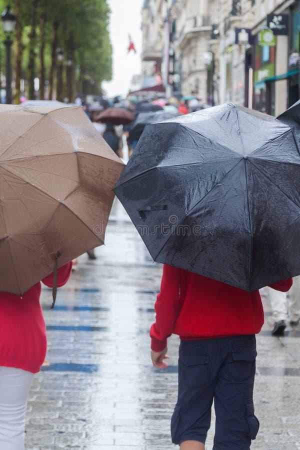 Les gens avec des parapluies de pluie dans la ville pluvieuse image libre de droits