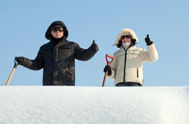 Les gens avec des pelles pour le déblaiement de neige photos stock