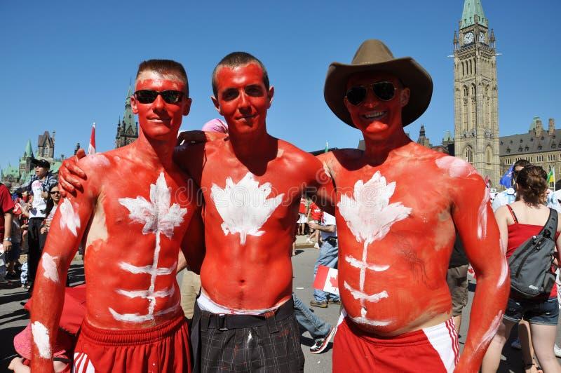 Les gens avec la peinture de fuselage en jour du Canada image libre de droits