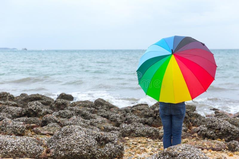 Les gens avec le parapluie d'arc-en-ciel au bord de la mer image libre de droits