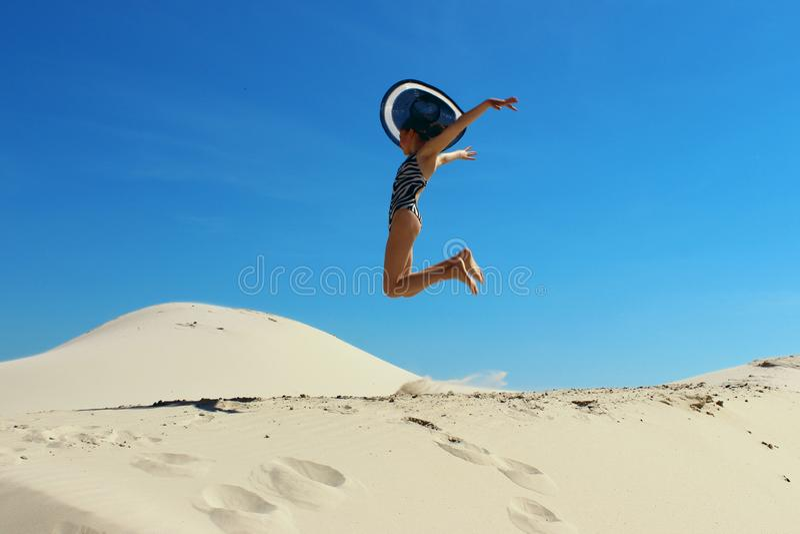 Les gens, bonheur, concept de voyage Adolescente utilisant un grand chapeau noir sautant sur une plage Fille attirante sautant su photo stock