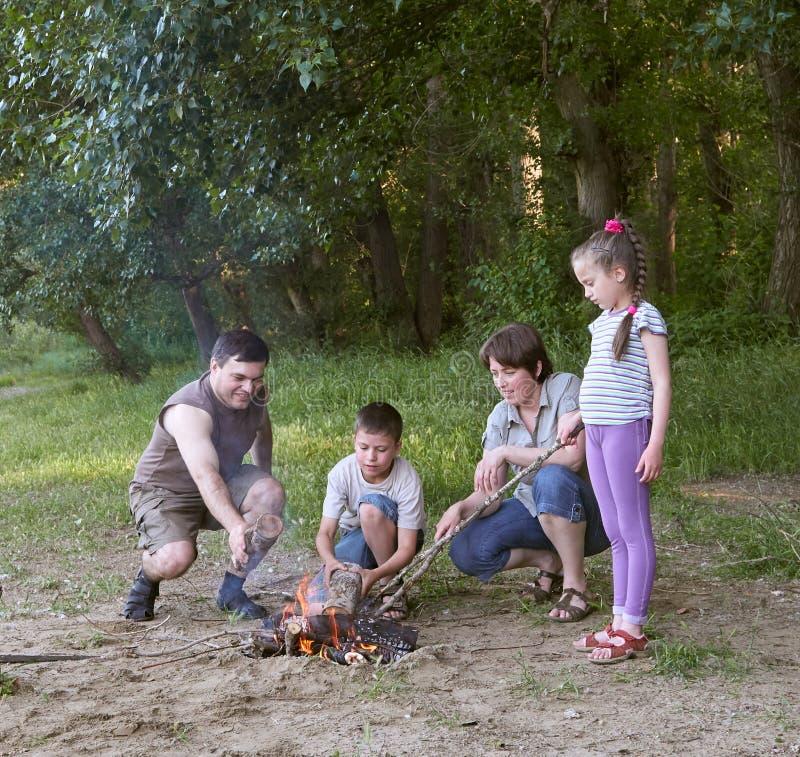 Les gens campant dans la forêt, active de famille en nature, allument le feu, saison d'été image libre de droits