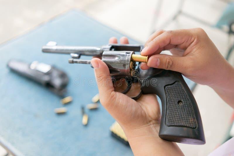 Les gens chargent des balles dans l'arme à feu de revolver photographie stock